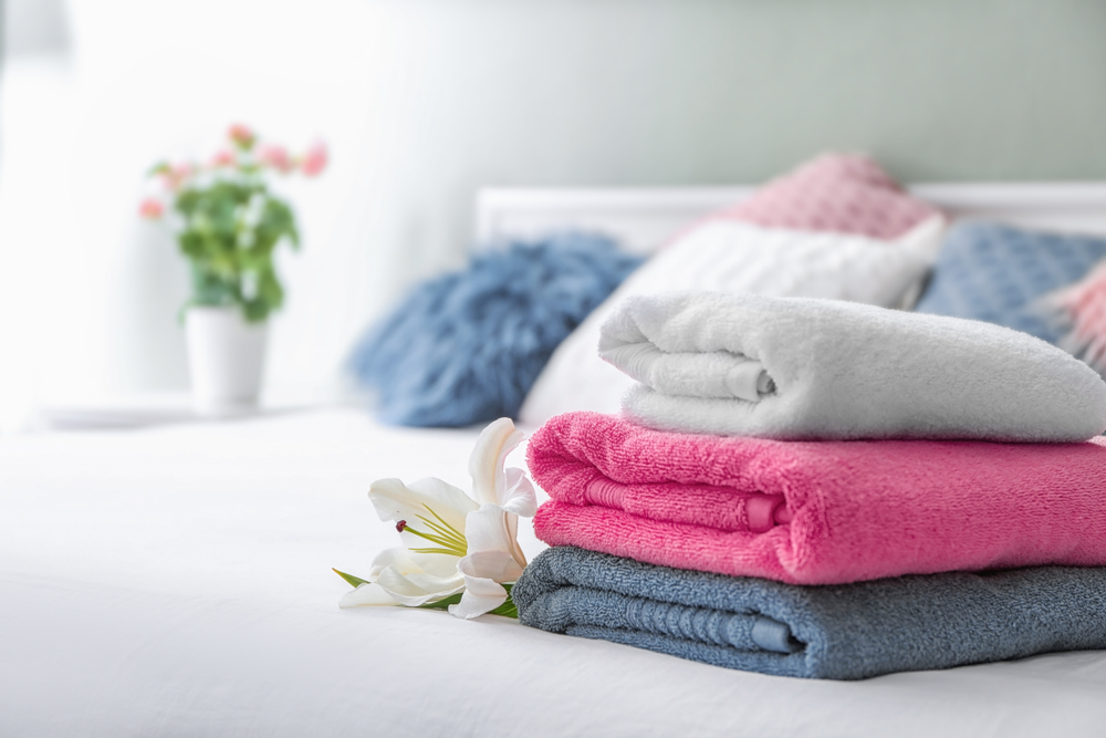 Stack,Of,Clean,Towels,On,Bed